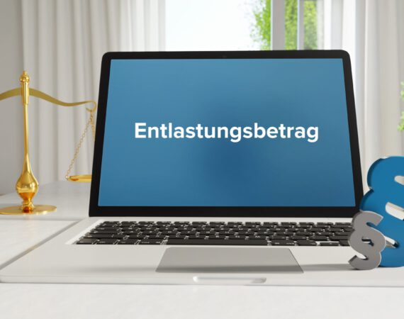 Entlastungsbetrag – Recht, Gesetz, Internet. Laptop im Büro mit Begriff auf dem Monitor. Paragraf und Waage.